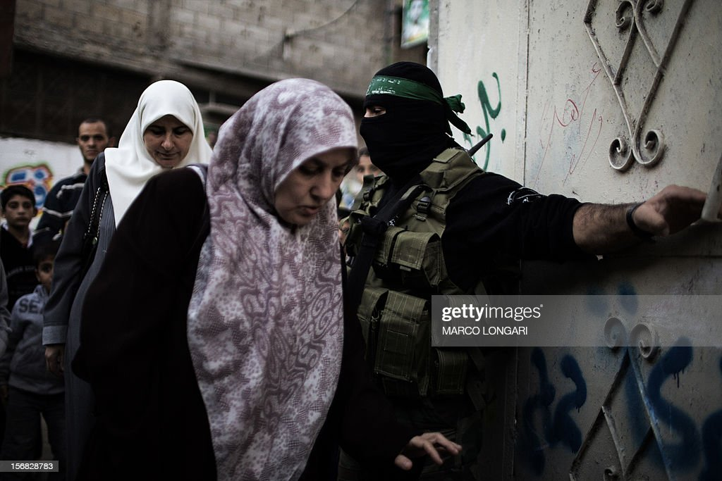 Palestinian women are let through by gunmen from the Ezzedine al-Qassam Brigades, the armed wing of Hamas, into the house of their late leader Ahmed Jaabari, as they visit his family to pay their condolences in Gaza City on November 22, 2012. Israeli politicians returned to the campaign trail as the streets of Gaza came back to life after a truce ended eight days of bloodshed, with both sides claiming victory while remaining wary.