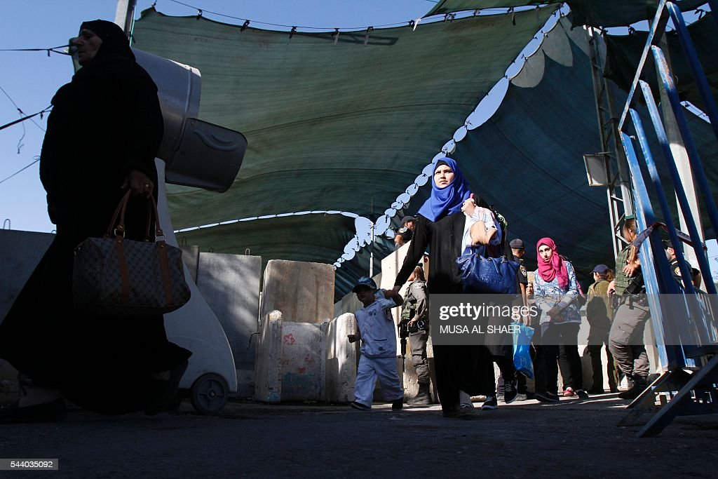 Palestinian women cross an Israeli checkpoint between the West Bank town of Bethlehem and Jerusalem, heading to Jerusalem's Al-Aqsa Mosque compound on the forth and last Friday of the Muslim holy month of Ramadan on July 1 , 2016. Israeli authorities announced on June 28 they were closing Jerusalem's flashpoint Al-Aqsa mosque compound to non-Muslim visitors until the end of the Muslim holy month of Ramadan after a series of clashes between worshippers and Israeli police. Clashes have been taking place every morning since the beginning of the week over Jewish visits to the site, with youths throwing stones and security forces firing tear gas and sponge-tipped bullets. / AFP / MUSA