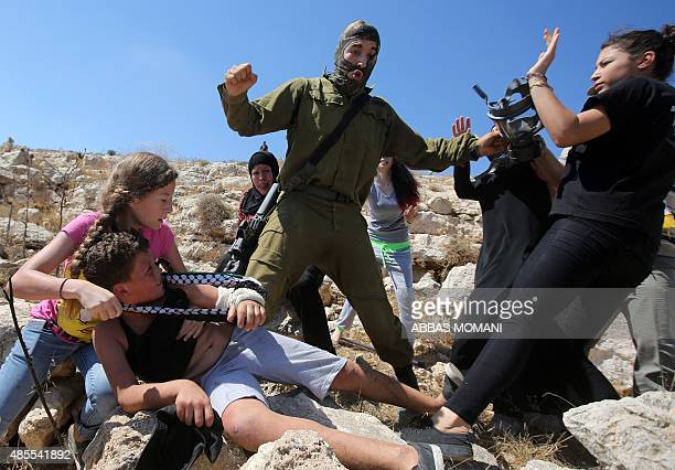 Palestinian women figth to free a Palestinian boy held by an Israeli soldier during clashes between Israeli security forces and Palestinian...