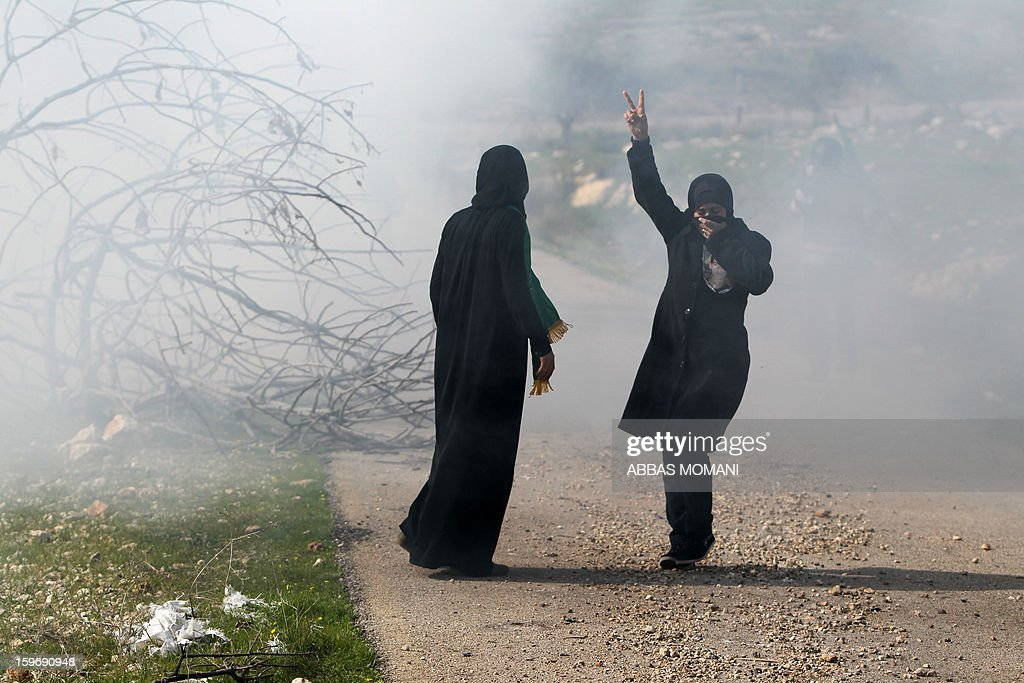 Palestinian women flash the victory sign as they cover their faces from tear gas fired by Israeli soldiers during a demonstration in the village of Budrus, west of Ramallah, on January 18, 2013. The Palestinians are bracing for a new right-wing government that Israel's election is expected to produce, hoping that international and domestic moves will strengthen their position.