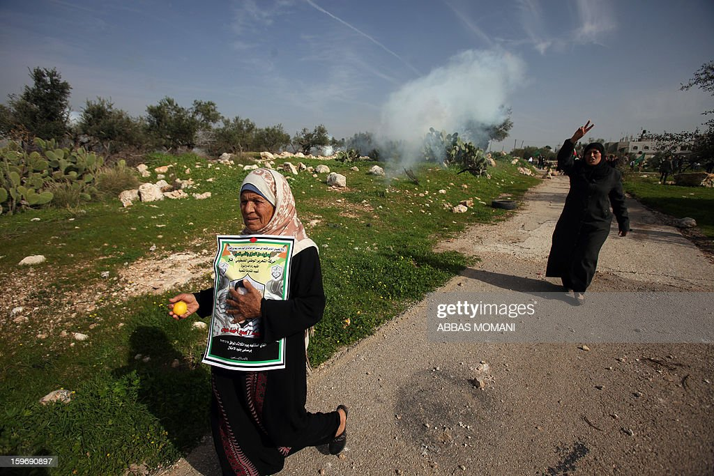 Palestinian women flash the victory sign as they run for cover from tear gas fired by Israeli soldiers during a demonstration in the village of Budrus, west of Ramallah, on January 18, 2013. The Palestinians are bracing for a new right-wing government that Israel's election is expected to produce, hoping that international and domestic moves will strengthen their position. AFP PHOTO / ABBAS MOMANI