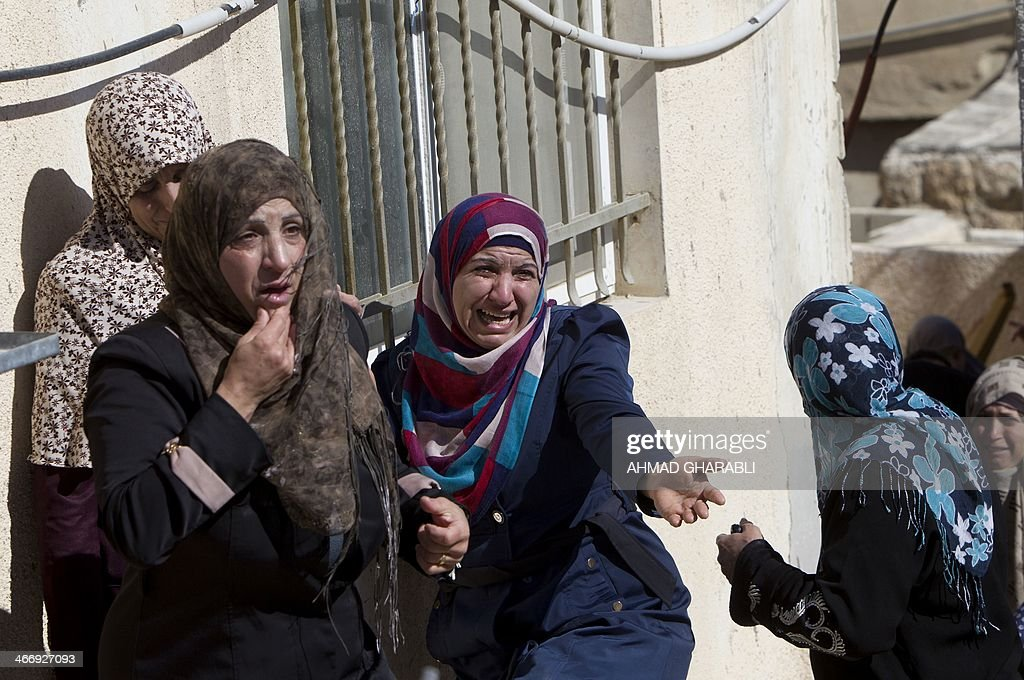 Palestinian women from the Beshr family react as Israeli municipality workers (unseen) demolish their house that the Israeli authorities said was built without municipal permission, on February 5, 2014 in the Arab east Jerusalem neighborhood of Jabel Mukaber. Israel pushed forward with plans for more than 550 new homes in three settlement neighbourhoods of annexed east Jerusalem, the city council said.