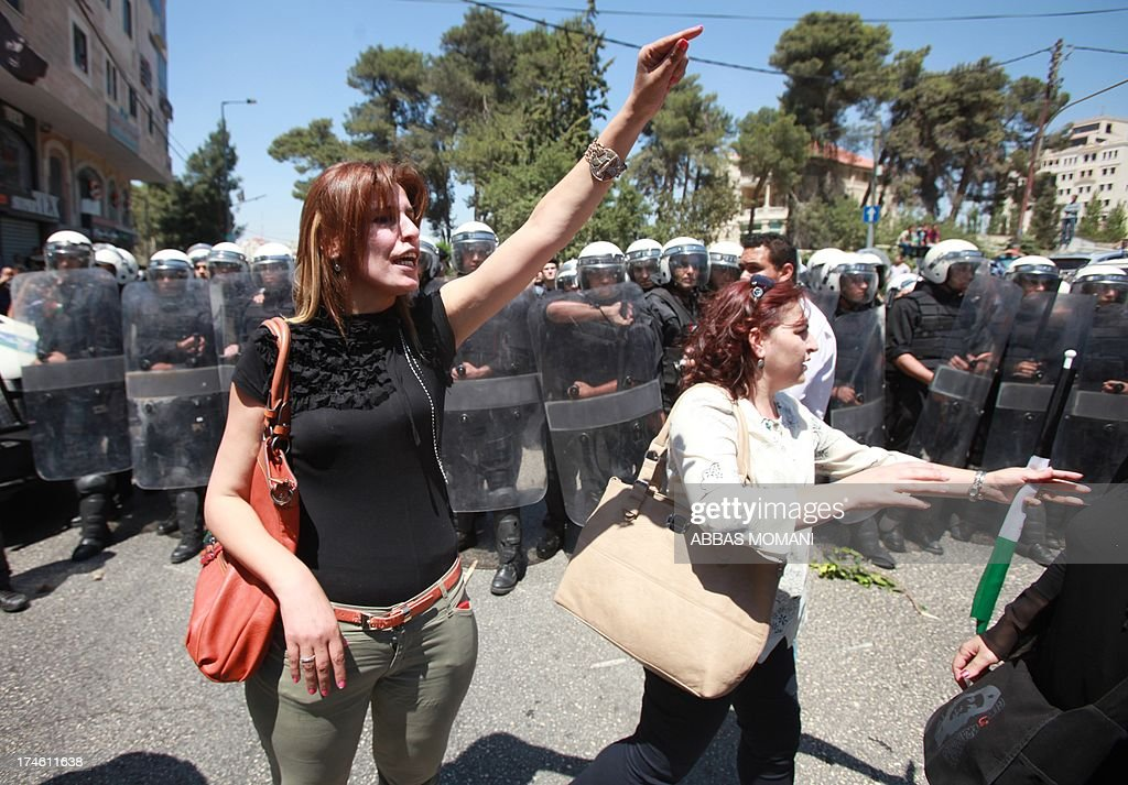 Palestinian women gesture at riot police as the demonstrate against the upcoming negotiations between Palestinian leaders and Israel, march towards the headquarters of Palestinian president Mahmud Abbas, in the West Bank city of Ramallah on July 28, 2013. A Palestinian official told AFP that the US-brokered renewal of peace talks, stalled since September 2010, would open in Washington this coming week.