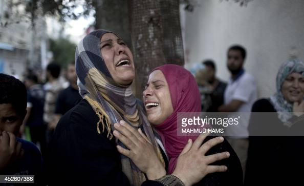 Palestinian women grieve over the death of relatives outside the morgue of the Kamal Adwan hospital in Beit Lahiya on July 24 after a UN school in...
