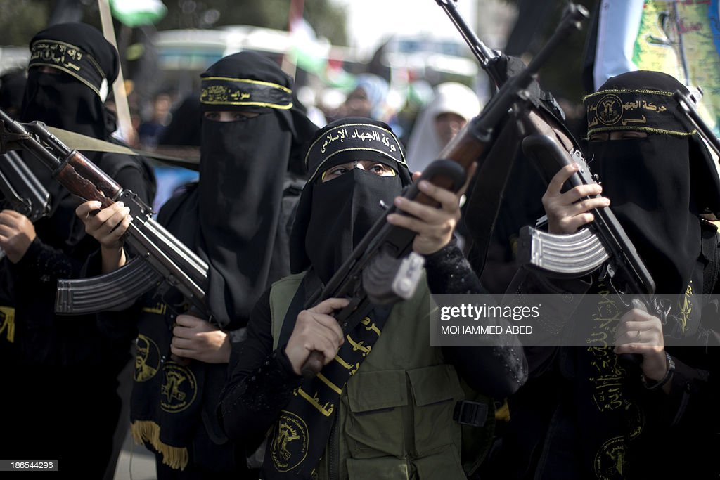 Palestinian women hold assult rifles as supporters of the Islamic Jihad rally to mark the anniversary of the movement's foundation in Gaza City, on November 1, 2013.
