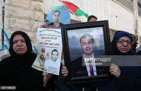 Palestinian women hold photos of their relatives who were allegedly involved in attacks and consequently killed by Israeli forces during a...