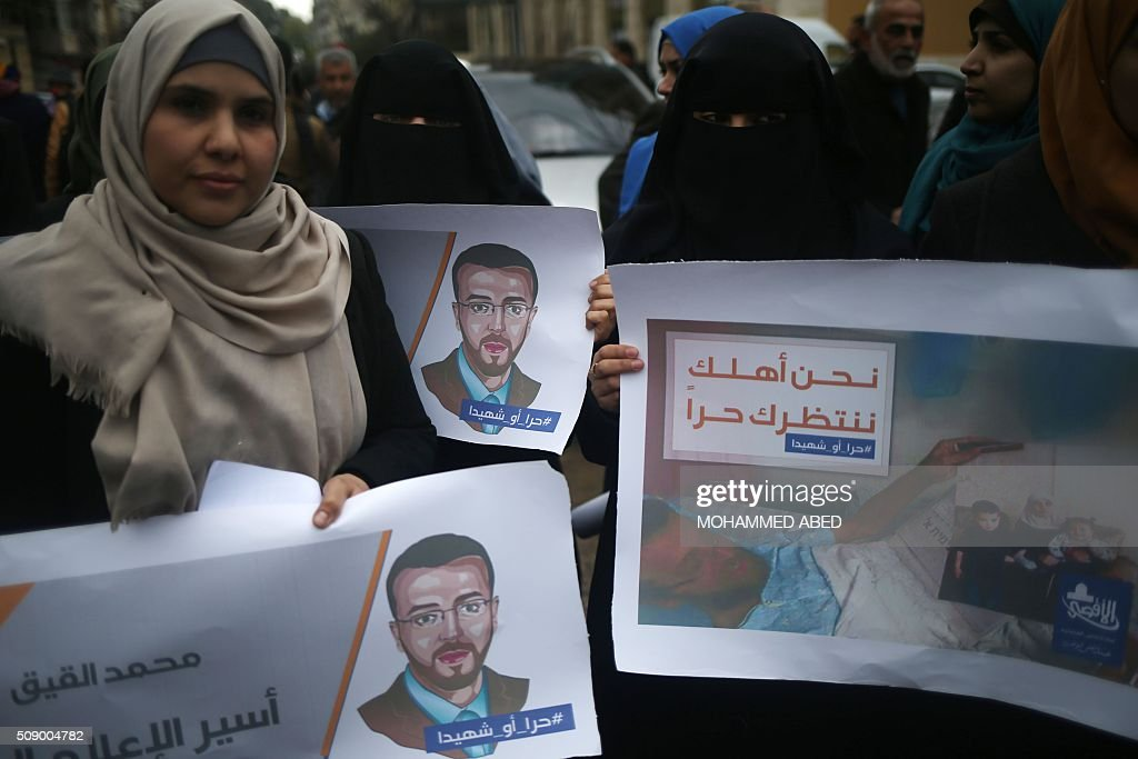 Palestinian women hold portraits of hunger striking Palestinian journalist Mohammed al-Qiq as they demonstrate in solidarity with him, on February 8, 2016, in Gaza City. The 33-year-old television reporter will keep up his 10-week hunger strike despite Israel suspending a detention without trial order against him, his lawyer said. / AFP / MOHAMMED ABED