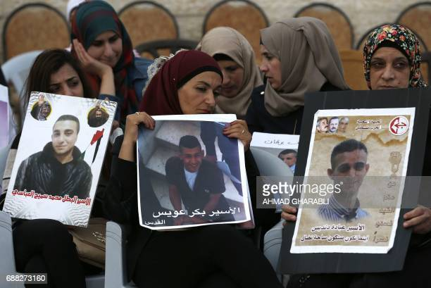 TOPSHOT Palestinian women hold portraits of relatives imprisoned in Israeli jails during a protest in front of the Red Cross offices in east...