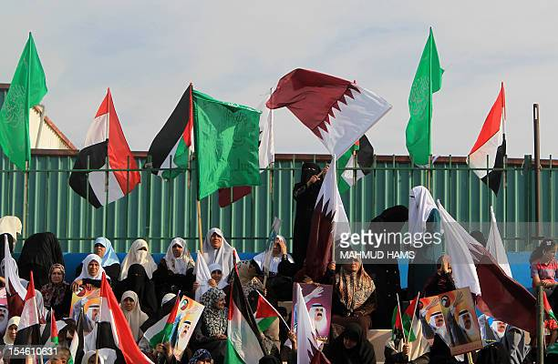 Palestinian women hold Qatari and their national flags alongside pictures of the Emir of Qatar Sheik Hamad bin Khalifa alThani as they wait for his...