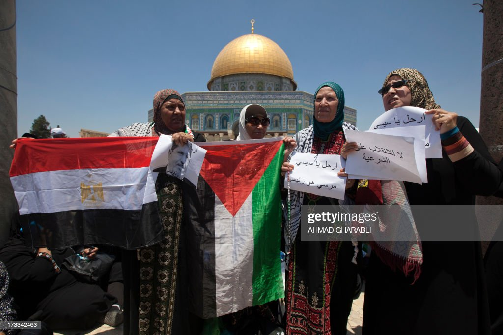 Palestinian women hold their national flag (C) and the Egyptian flag (L) alongside banners supporting Egypt's ousted president Mohamed Morsi as they gather outside the Dome of the Rock at the Al-Aqsa Mosque compound in Jerusalem for the first Friday prayers of the Muslim holy fasting month of Ramadan on July 12, 2013. During Ramadan, one of the five main religious obligations under Islam, Muslims are required to abstain from food and from drinking liquids, smoking and having sex from dawn until dusk. AFP PHOTO/AHMAD GHARABLI