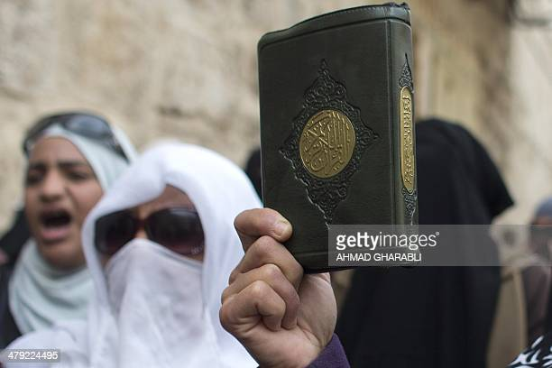 Palestinian women hold up copies of the Koran Islam's holy book as they protest after Israeli police blocked the entrance to the alAqsa Mosque...