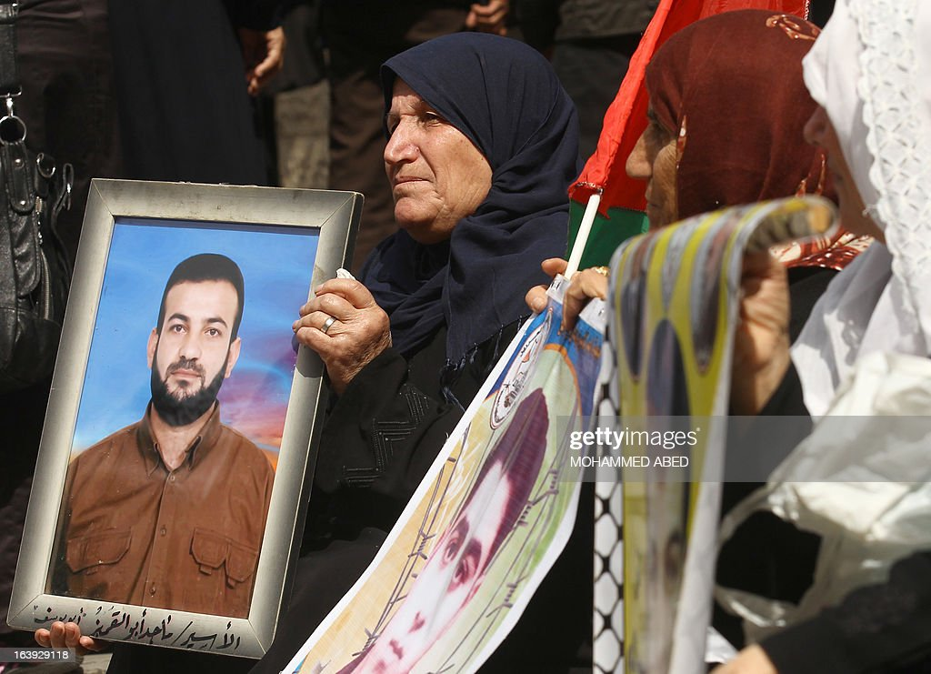 Palestinian women hold up photos of loved ones being held in Israeli prisons as they protest calling for the release of Palestinian prisoners outside the Red Cross offices in Gaza City on March 18, 2013.