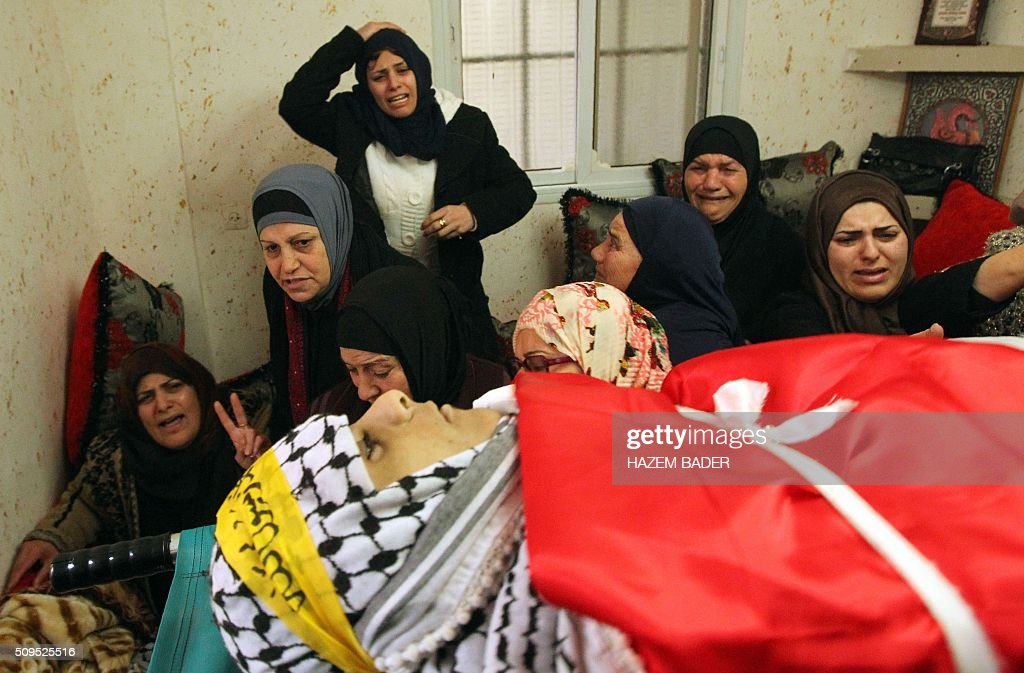 Palestinian women mourn over the body of Omar Jawabra, who was killed by Israeli fire during clashes near hebron the day before, during his funeral at al-Aroub Palestinian refugee camp, north the West Bank town of Hebron on February 11, 2016. / AFP / HAZEM BADER