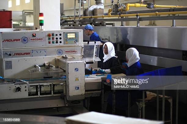 Palestinian women pack boxes of biscuits at the alAwda factory in Deir alBalah in the central Gaza strip on October 10 2012 The World Food Program...
