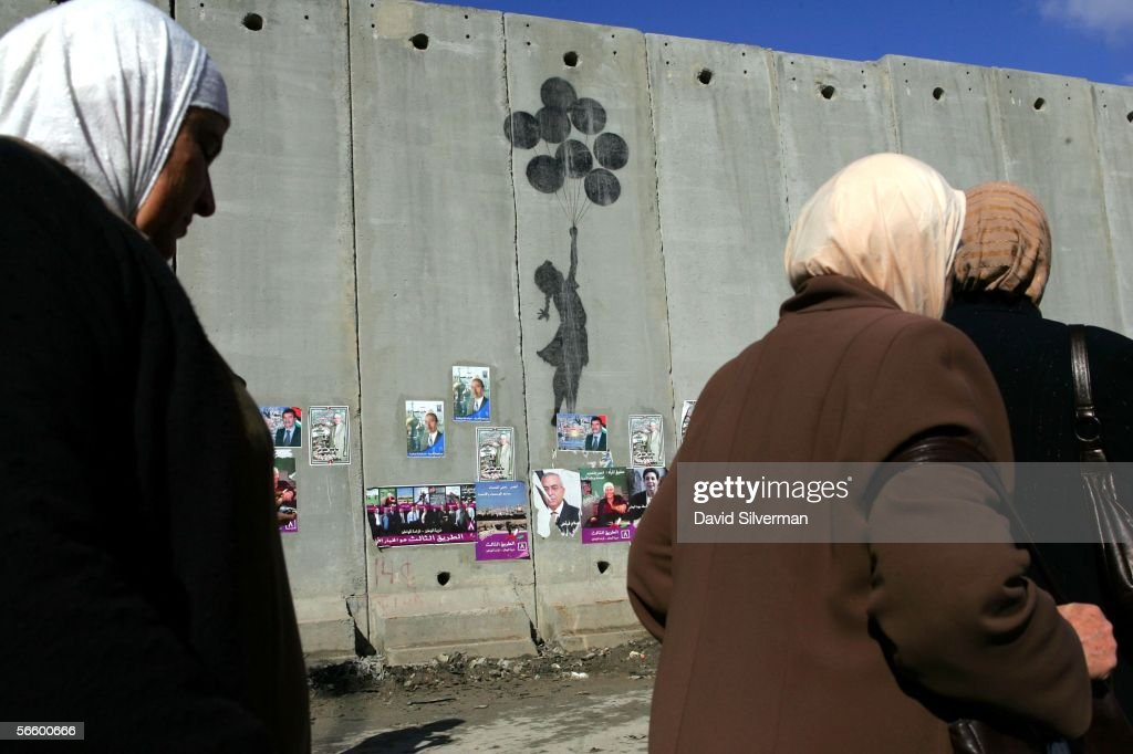 Palestinian women pass grafitti by the British artist Banksy on Israel's separation wall January 16, 2006 near the Israeli army's Qalandia checkpoint between Jerusalem ans Ramallah in the West Bank. The wall is covered with posters for candidates in the upcoming Palestinian parliamentary elections which are scheduled to take place on January 25.