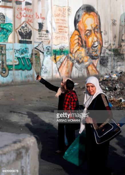 Palestinian women pose for a 'selfie' photograph with a cell phone as they wait in queue by a mural of Fatah leader Marwan Barghuti painted on a...
