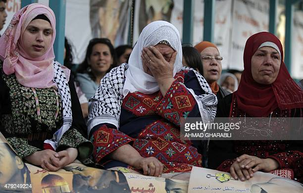 Palestinian women react during a demonstration in Shuafat in Israel annexed East Jerusalem on July 2 2015 to mark the first anniversary of the...