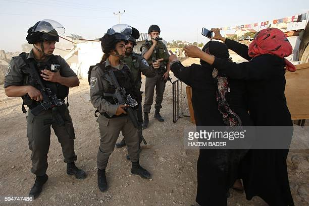 TOPSHOT Palestinian women react in front of Israeli border police as Israeli bulldozers destroy their homes and a community centre in the southern...