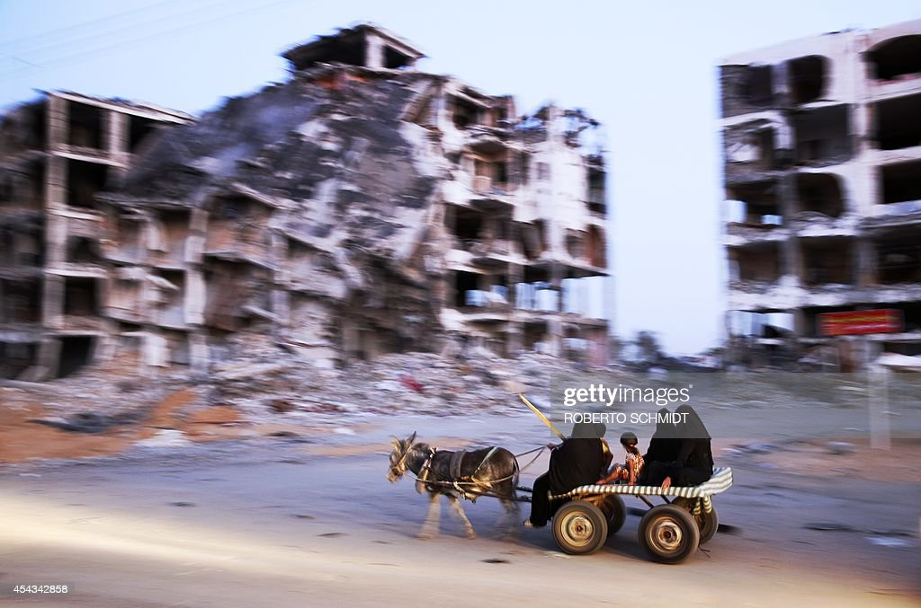 Palestinian women ride a donkey cart past a building complex that was destroyed by fighting between Hamas Militants and Israel on August 29, 2014 in the northern Gaza Strip city of Beit Hanun. Hamas chief Khaled Meshaal rejected any attempt to disarm his Palestinian Islamist movement in Gaza as demanded by Israel, saying the group's weapons were 'sacred'.