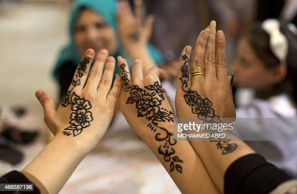 Palestinian women show their hands painted with traditional henna tatoos during the Palestinian Heritage Exhibition on the theme ''Products of our...