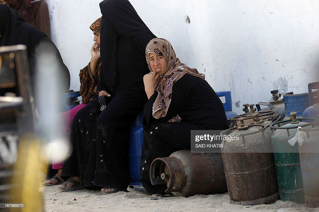 Palestinian women sit on empty bottles as they queue to have their cooking gas bottles refilled in Rafah, in the southern Gaza Strip on November 6, 2013. Palestinian officials said Israel has limited the quantity of cooking gas entering into Gaza, which causes a shortage.