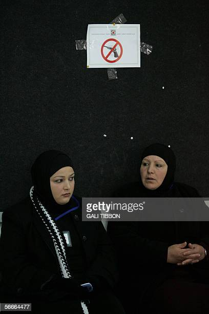 Palestinian women sit under a sign prohibiting weapons at a polling station in the West Bank town of Abu Dis on the outskirts of Jerusalem 25 January...