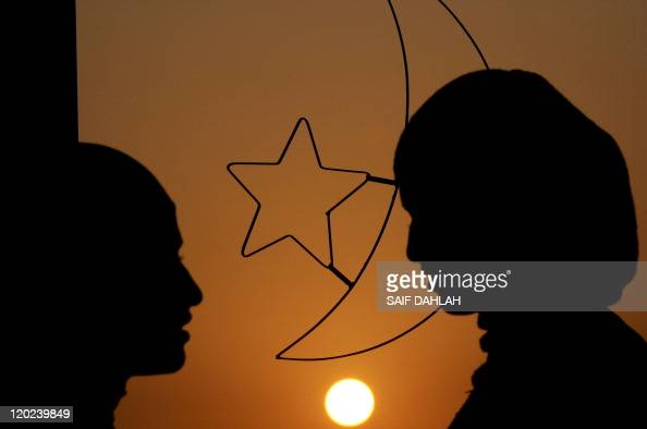 Palestinian women stand in front of a window decoration of Islam's crescent moon and a five branches star on the eve of Islam's holy fasting month of...