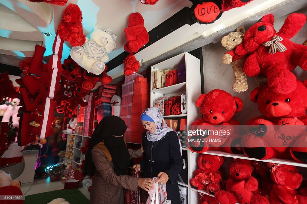 Palestinian women stand next to red teddy bears displayed at a gift shop on Valentine's Day on February 14, 2016 in Gaza City. / AFP / MAHMUD HAMS