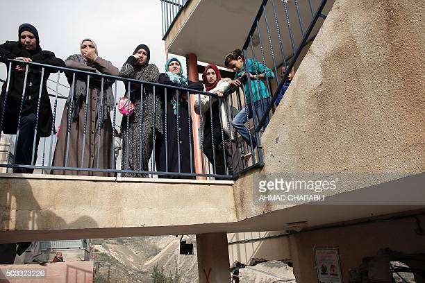Palestinian women standing on a balcony look at the damaged interior of the home of Bahaa Allyan a Palestinian who killed three Israelis in a...