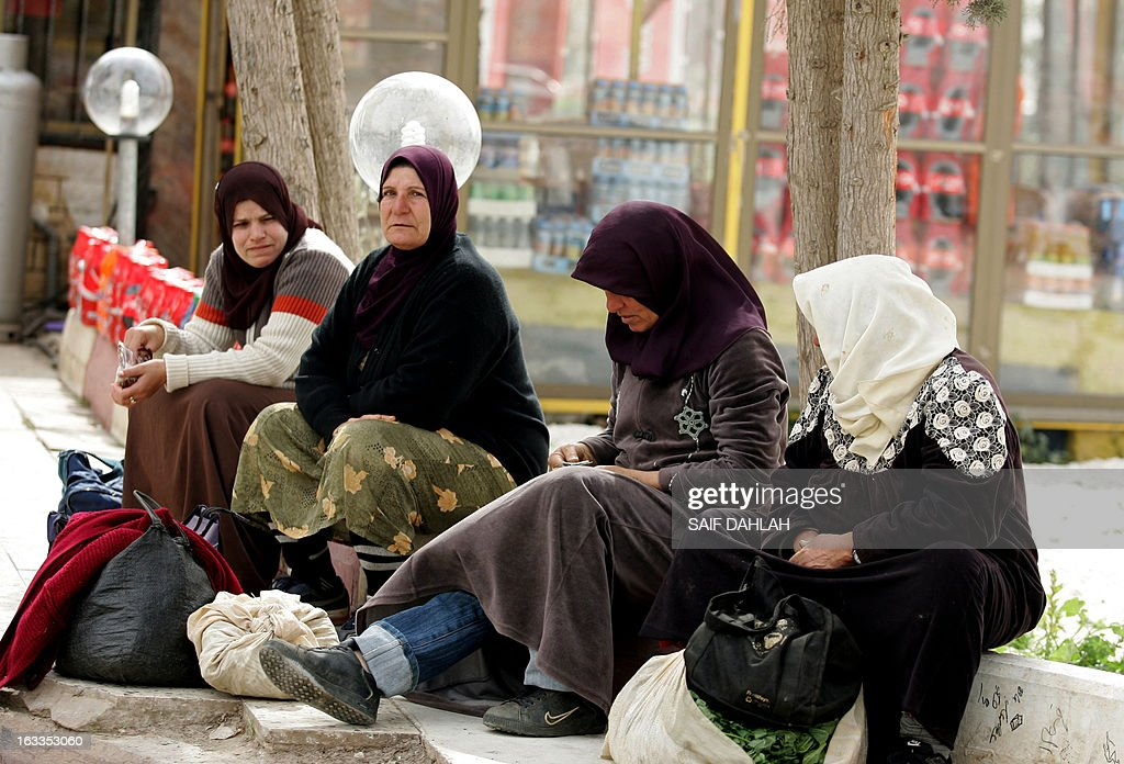 Palestinian women take a rest after crossing the Israeli Jalama checkpoint, near Jenin, as they return home to the West Bank after spending the day working in Israel on March 8, 2013, which marks International Women's Day across the globe.
