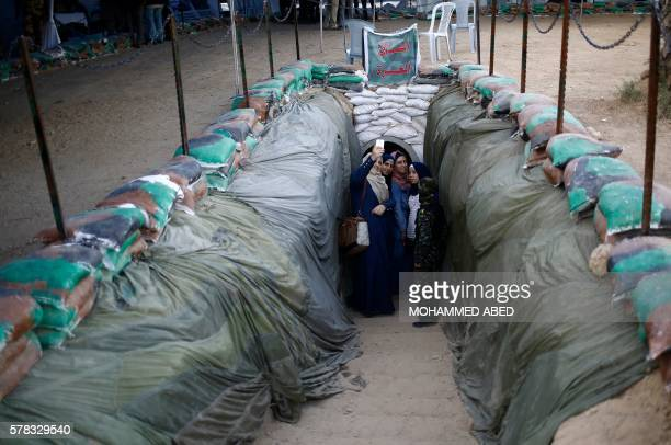 TOPSHOT Palestinian women take selfie infront of a tunnel used for military exercises during a weapon exhibition at a Hamasrun youth summer camp in...