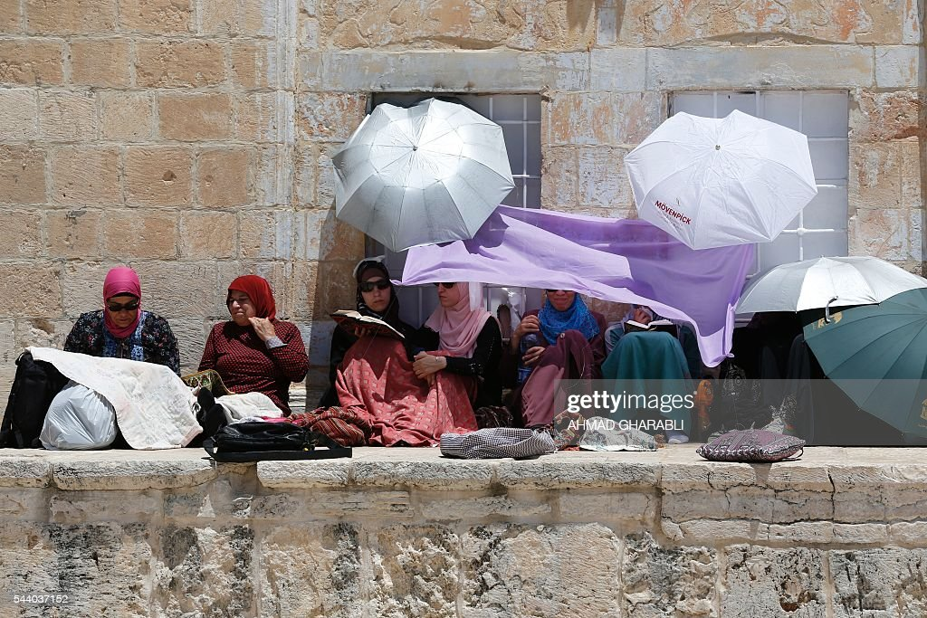 Palestinian women take shelter from the sun ahead of praying at the Dome of the Rock in Jerusalem's Al-Aqsa mosque compound during the last Friday prayers of the holy Muslim fasting month of Ramadan on July 1, 2016. / AFP / AHMAD
