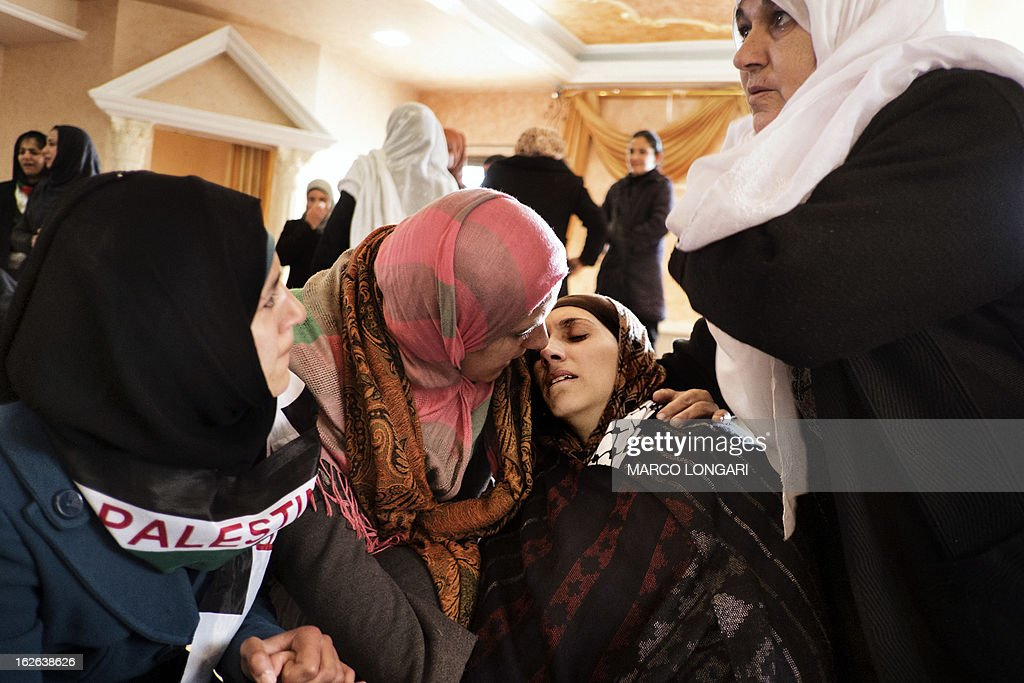 Palestinian women try to comfort Dalal (2nd-R), the widow of Arafat Jaradat, an inmate who died in an Israeli prison, during his funeral in the West Bank village of Saair on February 25, 2013. Militants of the Al-Aqsa Martyrs Brigades, the armed wing of Palestinian president Mahmud Abbas' Fatah movement, vowed to avenge the death of Jaradat, a prisoner they say was tortured in an Israeli jail.