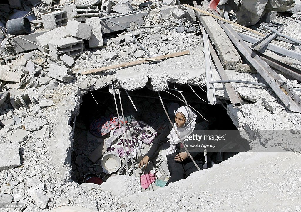 Palestinian women try to find usable belongings amongst the ruins of their buildings to keep living under hard conditions, after a permanent ceasefire between Palestinian groups and Israel, at jerry-built tents on their houses' ruins in Khan Yunis, Gaza on September 13, 2014.