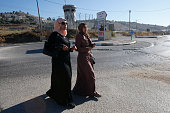 Palestinian women walk at a checkpoint blocking access to the alFawwar refugee camp south of the West Bank city of Hebron on July 26 before Israeli...