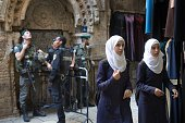 Palestinian women walk past an Israeli police checkpoint in Jerusalem's old city on October 8 under Israeli police presence due to high tension...