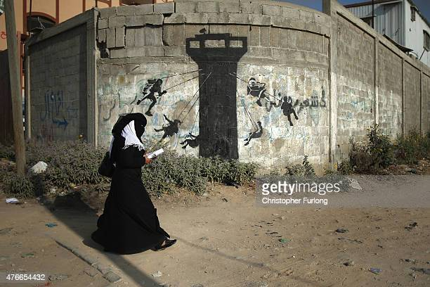 Palestinian women walk past graffiti by British artist Banksy as mounds of rubble and destroyed buildings continue to scar the landscape of Gaza on...
