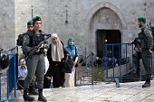 Palestinian women walk past Israeli border police at the Damascus Gate at the entrance of the Old City in east Jerusalem on October 14 2015 Israel...