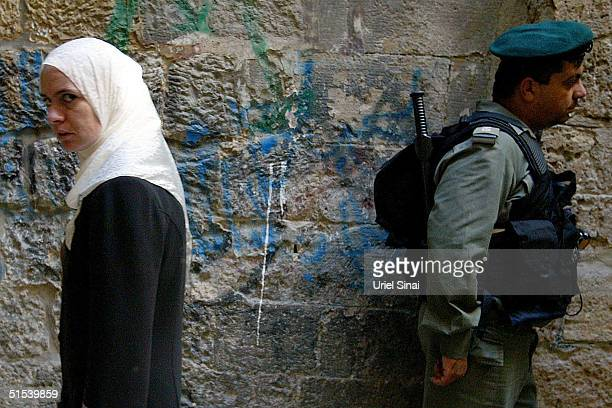 A Palestinian women walks past an Israeli border policemen as he stands guard outside the AlAqsa Mosque compound on the second Friday of the Muslim...