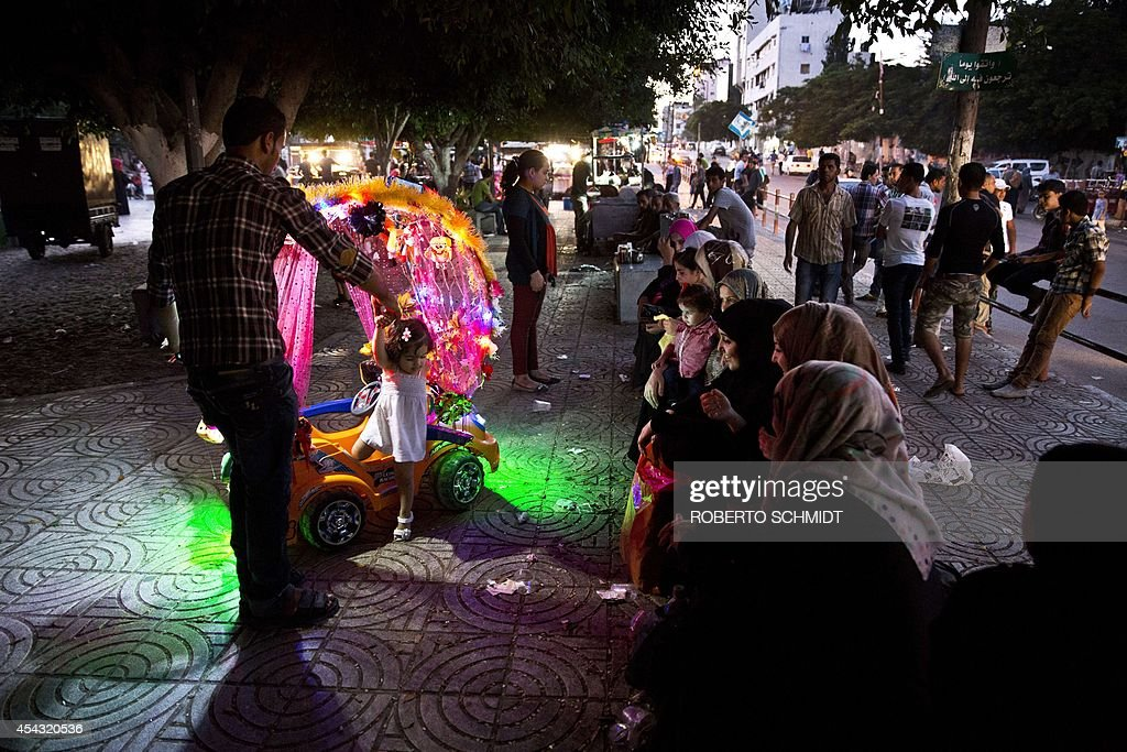 Palestinian women watch as a little girl gets help stepping off a push cart after getting a fun spin around a park in downtown Gaza City on August 28, 2014 one day after an unconditional ceasefire was signed between Hamas and Israel. Millions in and around the war-torn coastal enclave were enjoying a second day of peace after the guns fell silent. AFP PHOTO/ROBERTO SCHMIDT