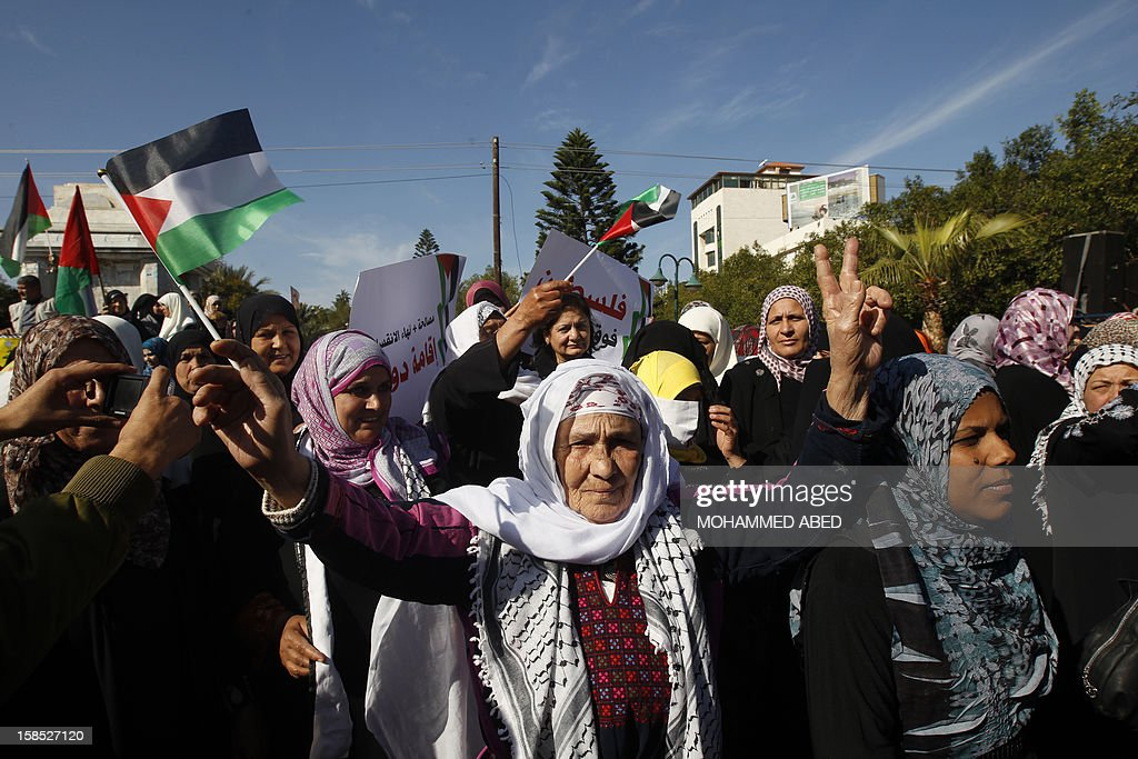 Palestinian women wave their national flag and chant slogans calling for an end to the political division between the Gaza Strip Hamas-led leadership and the Palestinian Authority's Fatah movement, during a protest in Gaza City on December 18, 2012.