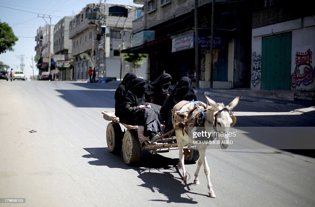 Palestinian women wearing the niqab ride on a donkey-pulled carriage in Beit Lahia in the northern Gaza Strip on September 6, 2013.