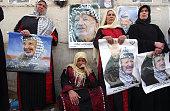 Palestinian women weep next to poster of the late Palestinian leader Yasser Arafat near the Muqata Ramallah compound on Nov 11 2004 Arafat was...