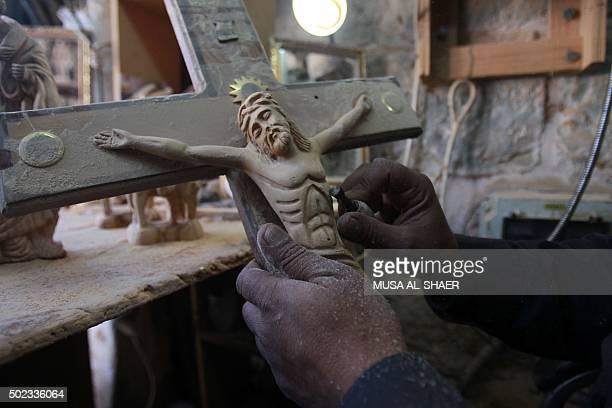 A Palestinian wood sculptor works on an olive wood crucifix at his workshop near Manger Square in the West Bank biblical city of Bethlehem on...