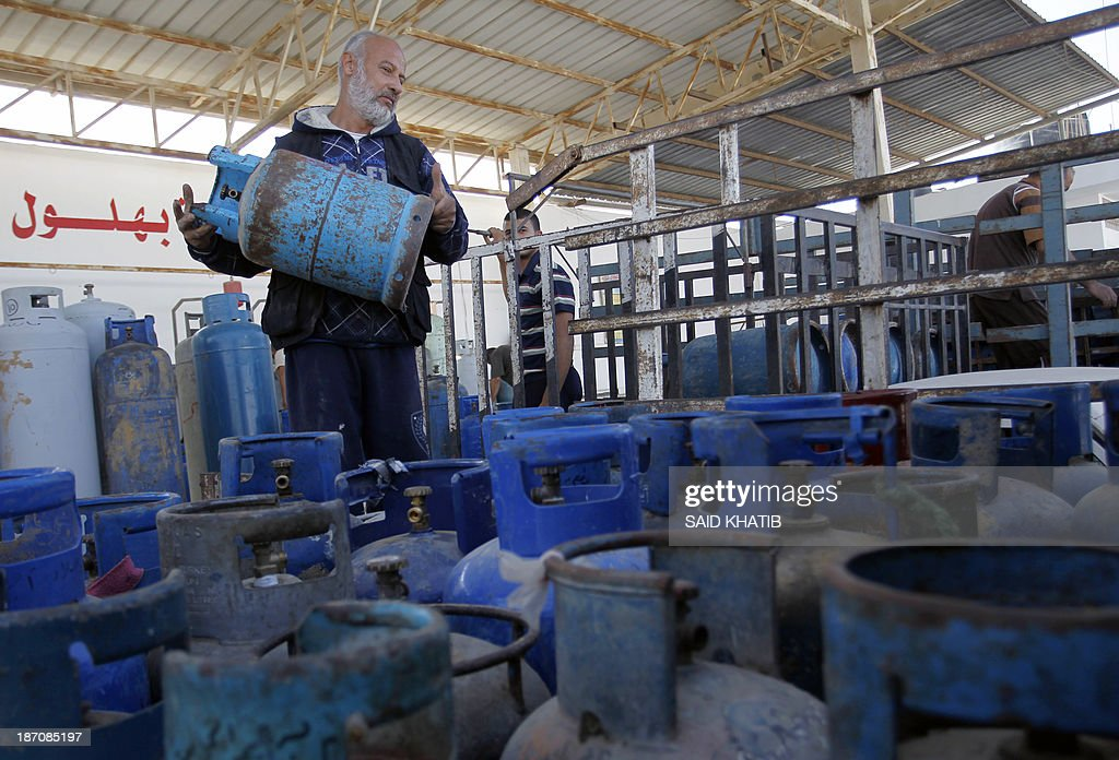A Palestinian worker carries a cooking gas bottle at a warehouse in Rafah, in the southern Gaza Strip on November 6, 2013. Palestinian officials said Israel has limited the quantity of cooking gas entering into Gaza, which causes a shortage. AFP PHOTO/ SAID KHATIB