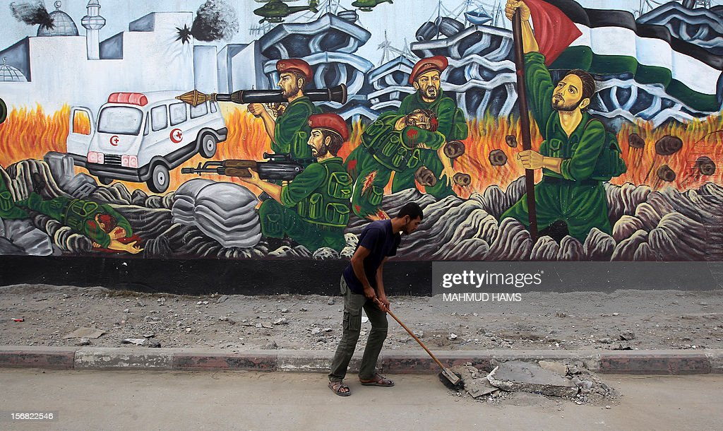 A Palestinian worker cleans the street in front of war graffiti near the destroyed Al-Saraya Hamas headquarters in Gaza City November 22, 2012. An Egypt-brokered truce took hold in the Gaza Strip, ending eight-day operation during which the Israeli army said it hit more than 1,500 targets, while Gaza militants fired 1,354 rockets over the border. AFP PHOTO/MAHMUD HAMS