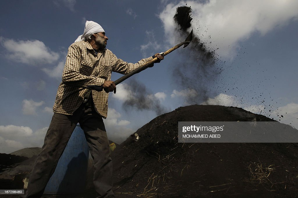 A Palestinian worker covers a hole producing smoke from under a pile of smoldering wood during the process of turning wood into coal at one of the few local charcoal manufacturing plants east of Gaza City on April 23, 2013.