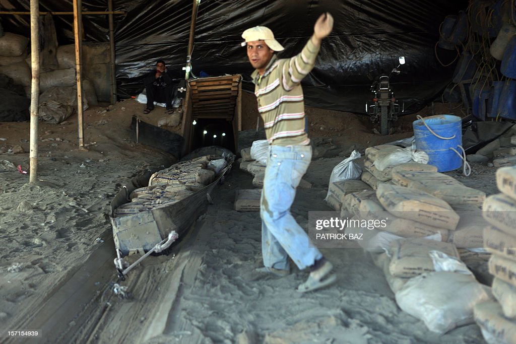 A Palestinian worker gestures as a slide loaded with Egyptian cement is pulled from a smuggling tunnel linking the Gaza Strip to Egypt in Rafah on November 29, 2012. Israeli airforce jets bombed most of the smuggling tunnels in the southern Gaza Strip during its war against the Islamist movement Hamas, which rules the coastal Palestinian territory, between 14 and 21 of November 2012.