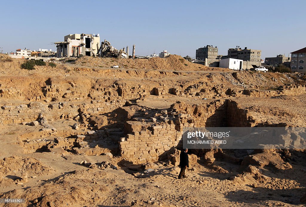 A Palestinian worker inspects the ancient archaeological site of Anthedon Harbour, also know as 'al-Blakhiyah', which is located next to a training site for Hamas military, in Gaza City on April 25, 2013. AFP PHOTO/MOHAMMED ABED