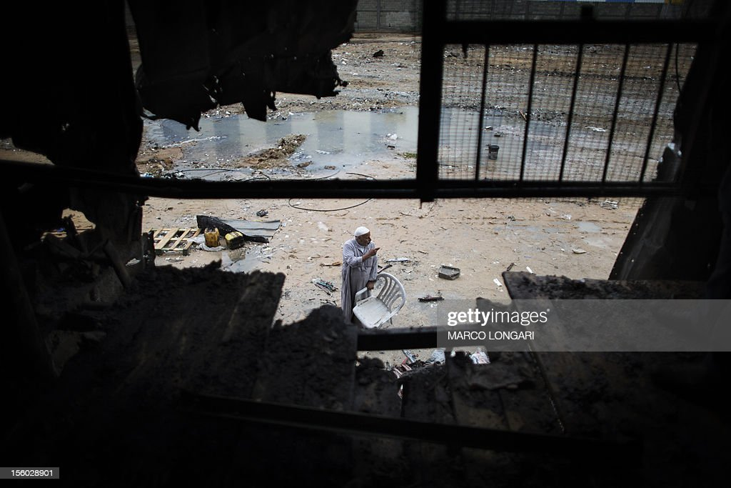 A Palestinian worker is seen through a hole in the wall of a plastic factory that was damaged during Israeli artillery fire and shelling in Beit Hanun, in the northern Gaza Strip, on November 11, 2012. Five Gazans were killed and 30 injured by Israeli shelling after militants fired an anti-tank rocket at an Israeli jeep, wounding four soldiers, sources on both sides said.
